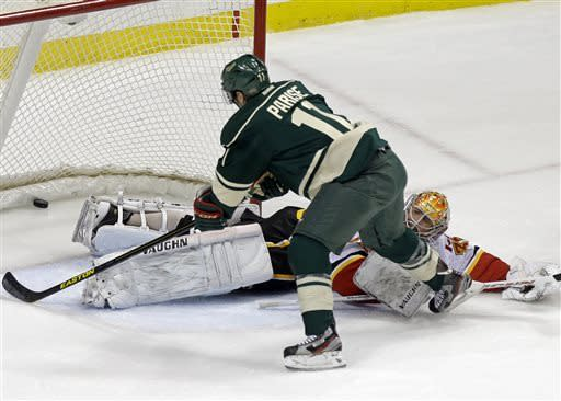 Minnesota Wild's Zach Parise, left, scores on Calgary Flames goalie Joey MacDonald in the first period of an NHL hockey game, Sunday, April 21, 2013, in St. Paul, Minn. (AP Photo/Jim Mone)