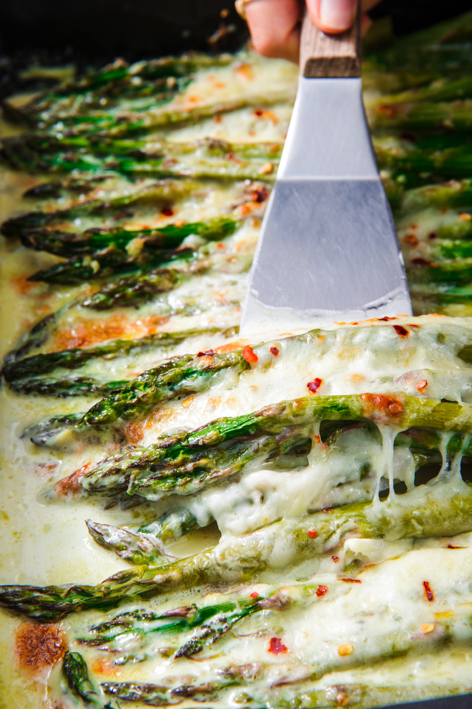 """<p>Our favourite way to prepare asparagus is as a fancy side: Top it with garlic, a little cream, Parmesan, and mozzarella and bake it until the cheese is bubbly and golden and the asparagus is tender. This will be gone in seconds.</p><p>Get the <a href=""""https://www.delish.com/uk/cooking/recipes/a31728813/cheesy-baked-asparagus-recipe/"""" rel=""""nofollow noopener"""" target=""""_blank"""" data-ylk=""""slk:Cheesy Baked Asparagus"""" class=""""link rapid-noclick-resp"""">Cheesy Baked Asparagus</a> recipe.</p>"""