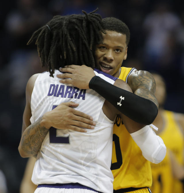 UMBC's Jairus Lyles, back, hugs Kansas State's Cartier Diarra (2) in the final moments of a second-round game in the NCAA men's college basketball tournament in Charlotte, N.C., Sunday, March 18, 2018. (AP Photo/Bob Leverone)