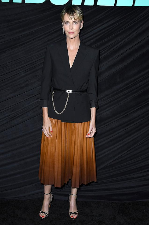 in a black chain-belted blazer, a Givenchy ombré brown pleated skirt and black strappy heeled sandals at the special screening <em>Bombshell</em> in West Hollywood.