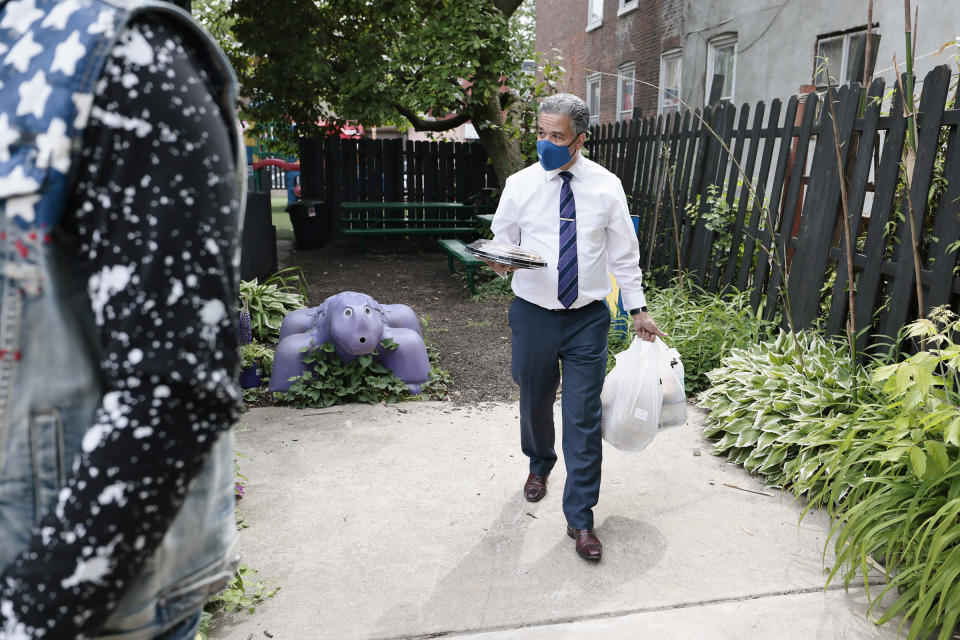 Philadelphia District Attorney candidate Carlos Vega brings food to his meet and greet event at Read Ready Daycare and Early Learning Academy in Philadelphia, on Sunday, May 16, 2021. Vega is challenging incumbent District Attorney Larry Krasner and both candidates are making a final push for votes before the election on May 18. (Elizabeth Robertson/The Philadelphia Inquirer via AP)