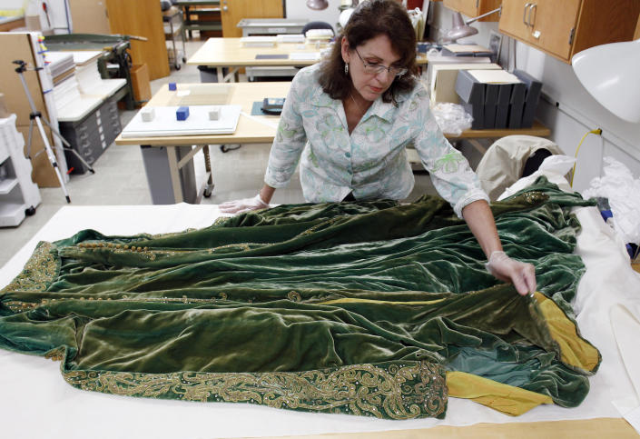 """Cara Varnell, an independent art conservator who specializes in Hollywood film costumes, works with the green velvet gown from the film """"Gone With the Wind,"""" Tuesday, July 19, 2011, in Austin, Texas. The Harry Ransom Center at the University of Texas is working to preserve five of the dresses acquired with the collection of film producer David O. Selznick in the 1980s. (AP Photo/Eric Gay)"""