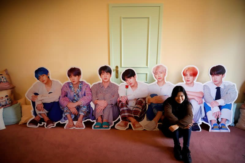 A fan of K-pop idol boy band BTS poses for photographs with cut-out of BTS at a pop-up store selling BTS goods in Seoul