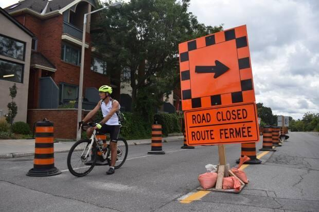 A man stops his bike at the intersection of Hawthorne and Colonel By Drive on Monday - the last day before a five-kilometre stretch of Colonel By reopens to motor vehicles. (Ben Andrews/CBC News - image credit)