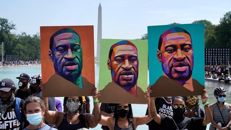 Attendees hold images of George Floyd as they participate in last year's March on Washington at the Lincoln Memorial in Washington, D.C. (Photo by Drew Angerer/Getty Images)