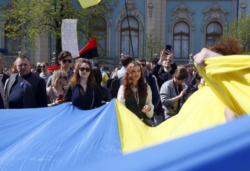People hold Ukrainian national flag in front of the parliament in capital Kiev, Ukraine, Thursday, April 25, 2019. Ukrainian lawmakers voted a draft law on the Ukrainian language, which provides for the mandatory use of the national language by government agencies, local self-government and in other spheres of public life. (AP Photo/Efrem Lukatsky)