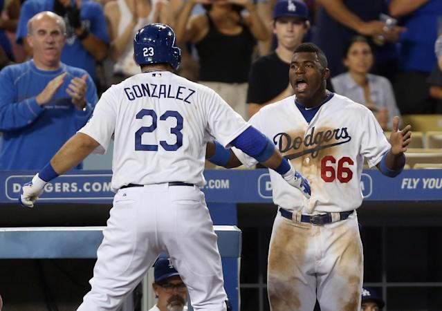 LOS ANGELES, CA - AUGUST 30: Adrian Gonzalez #23 of the Los Angeles Dodgers is congratulated by Yasiel Puig #66 after hitting a two-run home run against the San Diego Padres in the seventh inning at Dodger Stadium on August 30, 2013 in Los Angeles, California. (Photo by Jeff Gross/Getty Images)