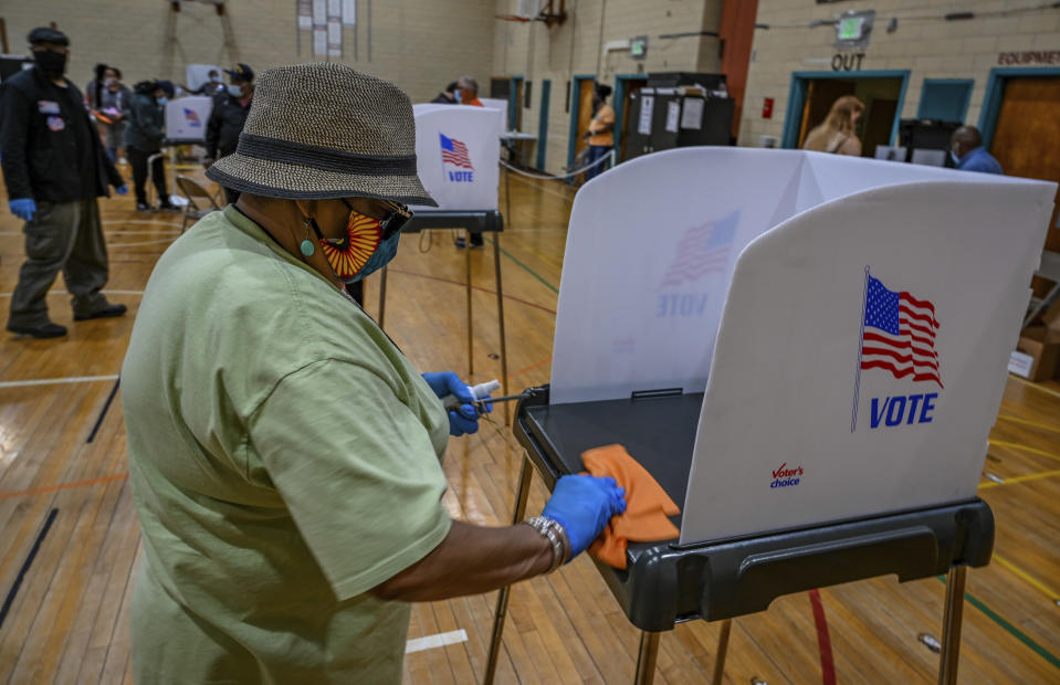 Election tech Veda Tucker sanitizes a voting booth between voters during the primary election in Baltimore, Tuesday, June 2, 2020. (Jerry Jackson/The Baltimore Sun via AP)