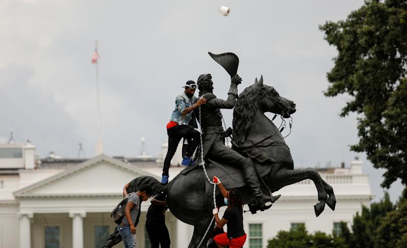 Protestors attach a chain to the statue of U.S. President Andrew Jackson in the middle of Lafayette Park in front of the White House in an attempt to pull it down as someone throws a roll of toilet paper at the statue during racial inequality protests in Washington, D.C., U.S., June 22, 2020. REUTERS/Tom Brenner TPX IMAGES OF THE DAY