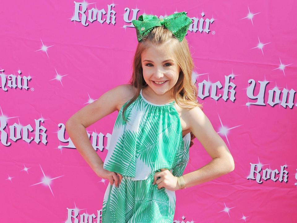 """a young (approximately 10 years old) piper rockelle in a green shirt, shorts, and bow standing on a pink red carpet. wall behind her reads """"rock your hair"""""""
