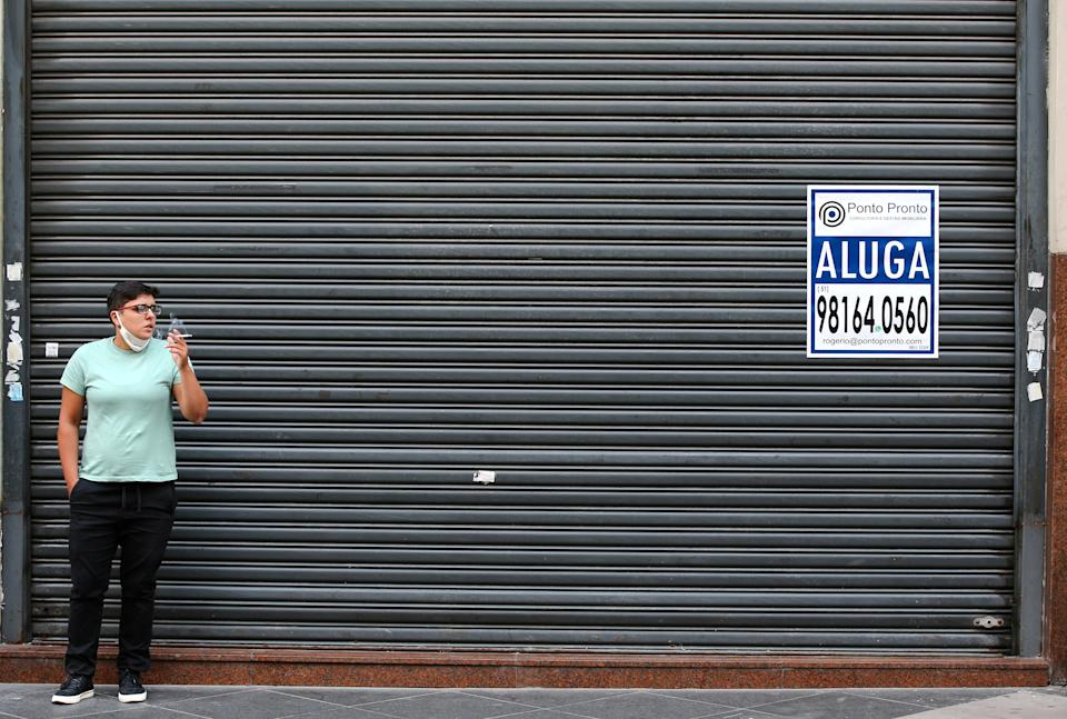A woman smokes in front of a closed store in downtown of Porto Alegre, after the Rio Grande do Sul state government mandated further restrictions to curb the spread of coronavirus disease (COVID-19), in Brazil March 3, 2021. REUTERS/Diego Vara