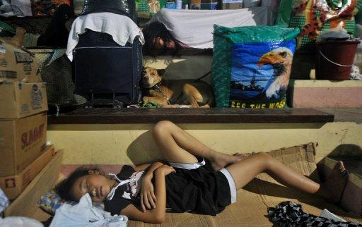 Displaced residents, seen here sleeping at a gymnasium in Iligan City, on December 24. Eight days after devastating flash floods swept to sea entire communities from the southern island of Mindanao, officials said 328,000 people were relying on emergency aid, including more than 69,000 sheltering at evacuation centres