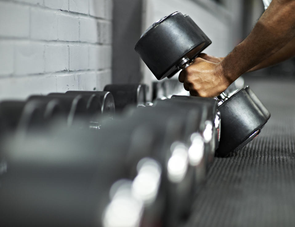 A man picks up weights off a rack in the gym.