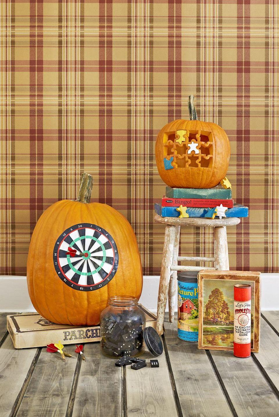 "<p>Scale the <a href=""https://www.countryliving.com/diy-crafts/how-to/a3048/halloween-templates-1009/"" rel=""nofollow noopener"" target=""_blank"" data-ylk=""slk:dartboard template"" class=""link rapid-noclick-resp"">dartboard template</a> up or down as necessary. Use template to cut 10 triangles from white contact paper and 10 triangles from black contact paper. Adhere to the pumpkin, lining up the edges, as shown above. Use template to cut rings from black, red, and green contact paper. Adhere the large black ring on the outside of the triangles, overlapping the edges slightly. Adhere the red ring along the inside edge of the black ring, overlapping edges slightly. Adhere the green ring on the dartboard. Use the template to cut small circles from green and red contact paper; adhere to the center of the board. Hot-glue silver cording along the seams of the white and black triangles. Adhere <a href=""https://www.amazon.com/Headline-Sign-31741-Letters-Numbers/dp/B000GP08K6/ref=sr_1_9?tag=syn-yahoo-20&ascsubtag=%5Bartid%7C10050.g.1350%5Bsrc%7Cyahoo-us"" rel=""nofollow noopener"" target=""_blank"" data-ylk=""slk:white vinyl stick-on numbers"" class=""link rapid-noclick-resp"">white vinyl stick-on numbers</a> on the black ring. Add darts as desired. </p><p><a class=""link rapid-noclick-resp"" href=""https://www.amazon.com/Tact-Creative-Covering-09F-C9933-12-Adhesive/dp/B001B02U5G/?tag=syn-yahoo-20&ascsubtag=%5Bartid%7C10050.g.1350%5Bsrc%7Cyahoo-us"" rel=""nofollow noopener"" target=""_blank"" data-ylk=""slk:SHOP CONTACT PAPER"">SHOP CONTACT PAPER</a><br></p>"