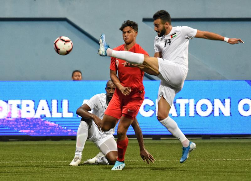 Singapore's Ikhsan Fandi (red jersey) tussles for the ball with Palestine's Abdallah Jaber in their 2022 World Cup qualifier at the Jalan Besar Stadium. (PHOTO: Football Association of Singapore)