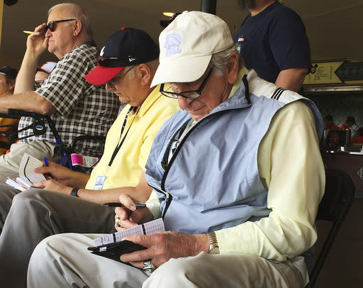 FILE - In this March 5, 2016, file photo, Tommy Giordano, right, special assistant to the general manager of the Atlanta Braves, scouts a spring training baseball game between the Braves and the Pittsburgh Pirates, in Kissimmee, Fla. Giordano spent nearly all of his marvelously full life as a baseball man. He was a major league player (for 11 games with the late, great Philadelphia Athletics), a minor-league manager, a front-office executive. More than anything, he was a scout, one of those guys who combed the backwoods and backwaters searching for the games next big star. (AP Photo/Paul Newberry, File)