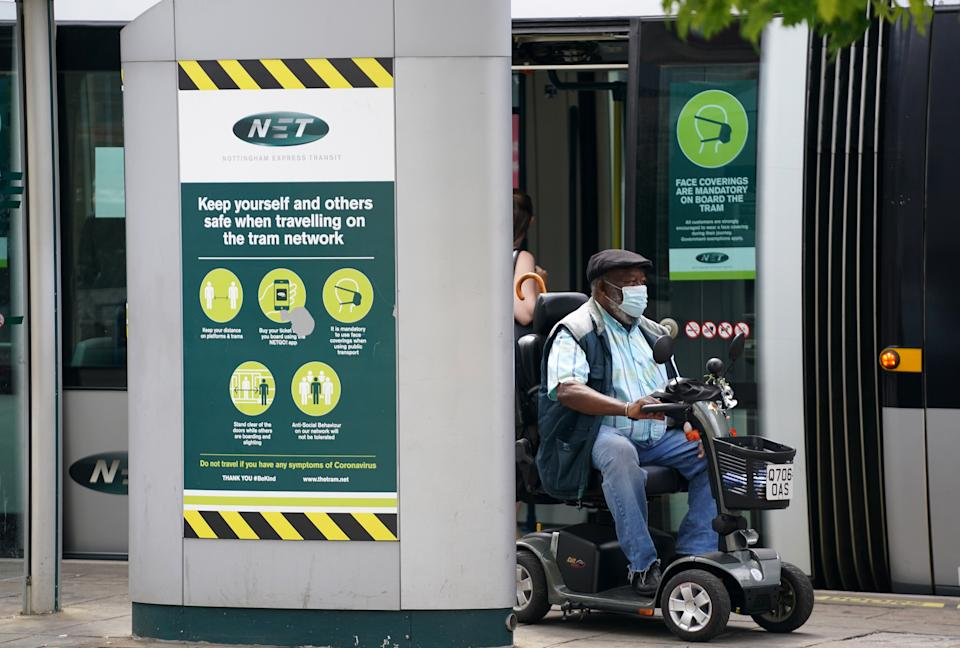 A member of the public wearing a mask riding a mobility scooter gets off the tram in Nottingham, during the easing of lockdown restrictions in England. Picture date: Wednesday July 14, 2021.