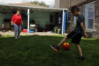 Eugenia Rodriguez, left, plays ball with her youngest son, Aaron, 6, in the backyard of her house Friday, July 2, 2021, in Chicago's Little Village neighborhood. Rodriguez hasn't been eligible for insurance coverage after overstaying a visitor visa from Mexico. She used to wake up every two or three hours at night to check on her mother. Since getting health insurance through the Illinois program, her mother has all the medications she needs. (AP Photo/Shafkat Anowar)