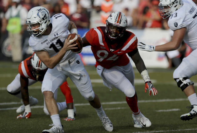Old Dominion quarterback Blake LaRussa is flushed out of the pocket by Virginia Tech's Trevon Hill during the second half of an NCAA college football game, Saturday, Sept. 22, 2018, in Norfolk, Va. Old Dominion won 49-35. (AP Photo/Jason Hirschfeld)