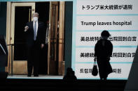 People walk past a screen showing the news report that President Donald Trump has left a hospital to return to the White House after receiving treatments for COVID-19, Tuesday, Oct. 6, 2020, in Tokyo. (AP Photo/Eugene Hoshiko)