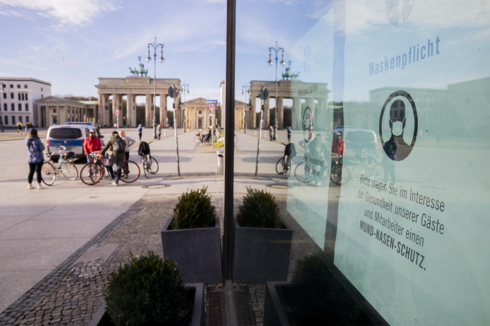 15 November 2020, Berlin: A sign for the mask duty hangs in front of the Brandenburg Gate on the window of a café. Photo: Christoph Soeder/dpa (Photo by Christoph Soeder/picture alliance via Getty Images)