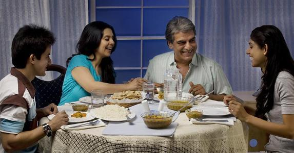 Family eating dinner at table, together copyright India Picture/Shutterstock.com