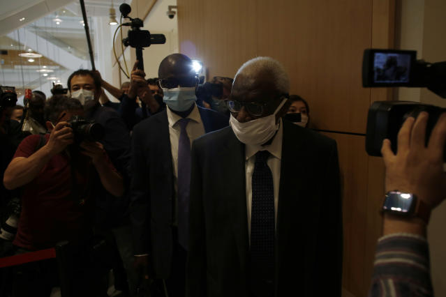 Former president of the IAAF (International Association of Athletics Federations) Lamine Diack, center, arrives at the Paris courthouse, Monday, June 8, 2020. A sweeping sports corruption trial opened Monday in Paris involving allegations of a massive doping cover-up that reached to the top of world track and field's governing body. Lamine Diack, 87, who served as president of the body for nearly 16 years, is among those accused of receiving money from Russian athletes to hide their suspected doping so they could compete at the Olympics in 2012 and other competitions. His son Papa Massata Diack is also charged in the case. (AP Photo/Thibault Camus)