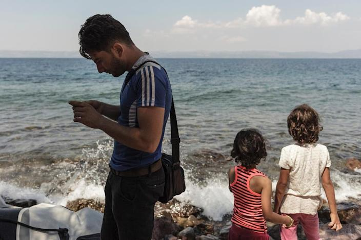 A Syrian man checks for mobile phone reception to inform his family that he arrived safely on the Greek island of Lesbos (AFP Photo/Achilleas Zavallis)
