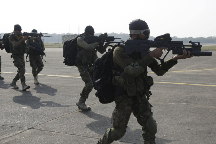 FILE - In this Dec. 10, 2018, file photo, Indian special force commandos take position after landing on a runway from a moving C-130 transport aircraft during India -U.S. joint air force drills at Air Force Station Kalaikunda, India. India has high hopes its ties with the United States will deepen under President Joe Biden, who was a key proponent of the 2008 civil nuclear deal between the countries and whose new administration includes several Indian Americans. (AP Photo/Bikas Das, File)