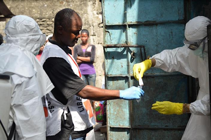 Medical workers, wearing protective suits, prepare prior to a burial for victims of the Ebola virus, in Monrovia, Liberia, on January 5, 2015 (AFP Photo/Zoom Dosso)