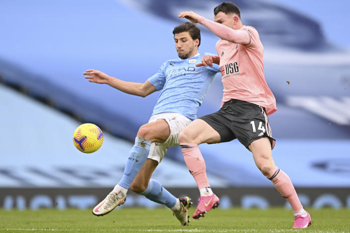Sheffield United's Oliver Burke, right, is challenged by Manchester City's Ruben Dias during the English Premier League match between Manchester City and Sheffield United at the the City of Manchester Stadium in Manchester, England, Saturday, Jan. 30, 2021. (Laurence Griffiths/Pool via AP)