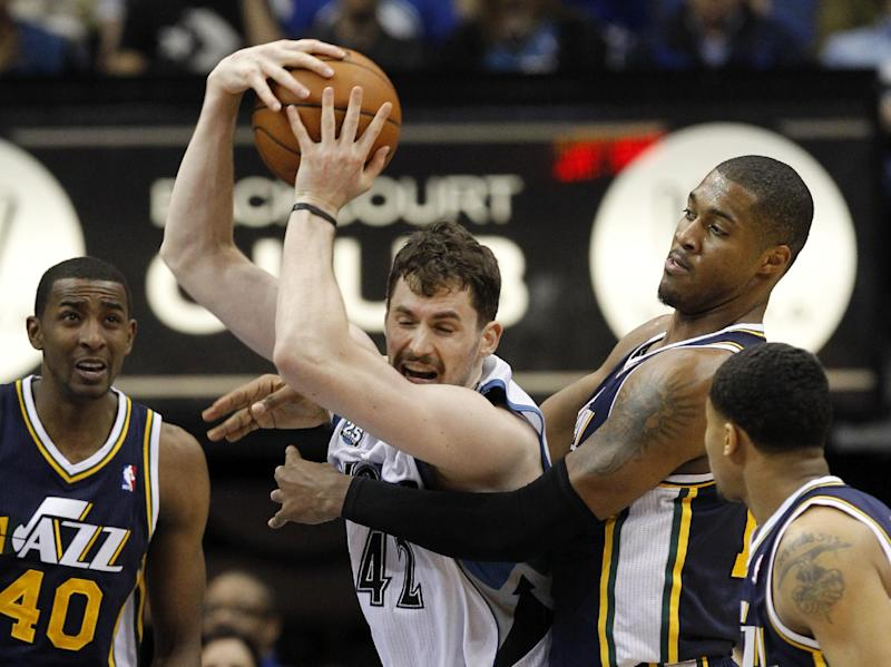Minnesota Timberwolves forward Kevin Love (42) wrestles a rebound away from Utah Jazz center Derrick Favors, second from right, as Jazz forward Jeremy Evans (40) watches during the fourth quarter of an NBA basketball game in Minneapolis, Wednesday, April 16, 2014. The Jazz won 136-130 in double overtime