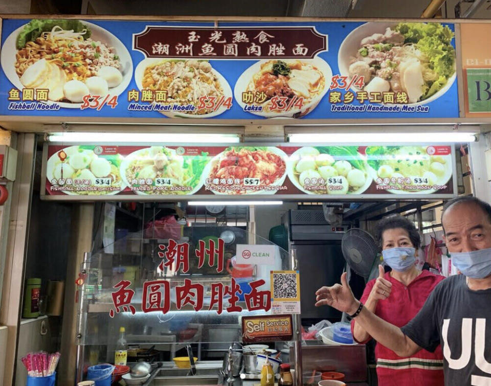 An elderly couple standing in front of their hawker stall