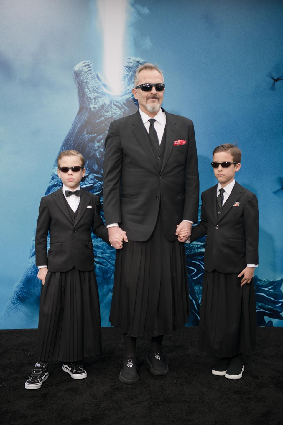 """HOLLYWOOD, CALIFORNIA - MAY 18: Miguel Bose and sons Diego and Tadeo arrive at the premiere Of Warner Bros. Pictures And Legendary Pictures' """"Godzilla: King Of The Monsters"""" at TCL Chinese Theatre on May 18, 2019 in Hollywood, California. (Photo by Morgan Lieberman/WireImage)"""