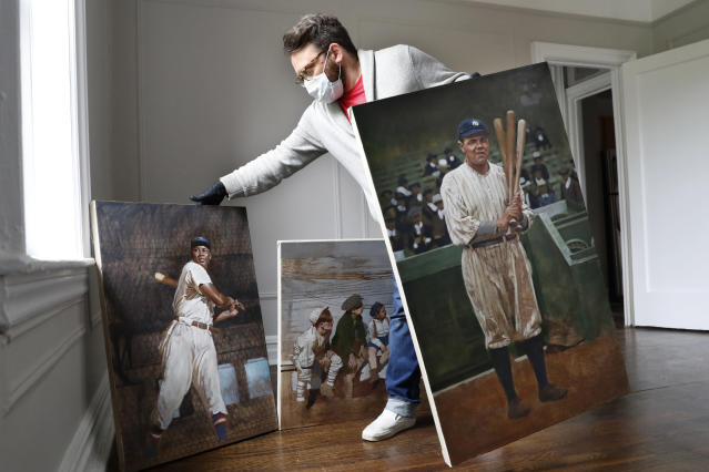 Baseball artist Graig Kreindler rearranges three of his paintings in progress, Wednesday, April 29, 2020, at his residence in the Brooklyn borough of New York. At left is a portrait of Hall of Famer and Negro Leagues catcher Josh Gibson showing off his swing, based on a photograph from 1939-40 season with the Cangrejeros (Crabbers) de Santurce, part of the Puerto Rican semi-professional baseball league. The painting at right depicts Babe Ruth during the 1920 season, Ruth's first with the Yankees, at the Polo Grounds, where the team played during most of the 1910's and 1920's before the Yankee Stadium was built in 1923. The middle painting shows some kids listening to Babe Ruth, who are obscured by Kreindler's right leg. (AP Photo/Kathy Willens)