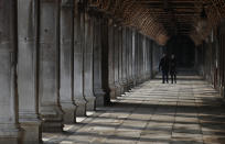 People walk down a passageway near St. Mark's Square in Venice, Italy, Saturday, Jan. 30, 2021. Gondolas and other vessels are moored instead of preparing for Carnival's popular boat parade in the lagoon. Alleys are eerily empty. Venetians and the city's few visitors stroll must be masked in public places, indoors and out, under a nationwide mandate. (AP Photo/Antonio Calanni)