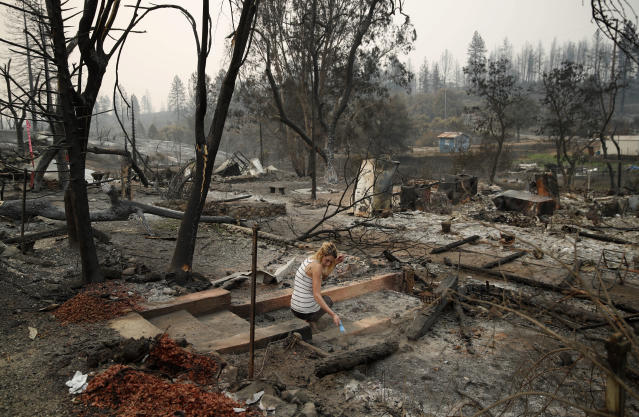 <p>Bree Seville uses a small brush to sweep the stairs leading to burned out ruins of her fiancee's mother's home in the Keswick area of Redding, Calif., Thursday, Aug. 9, 2018. (Photo: John Locher/AP) </p>