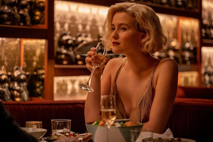 A blond woman in a gold dress sips from a champagne flute.