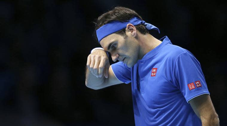 Switzerland's Roger Federer wipes his face during his ATP World Tour Finals singles final tennis match against Japan's Kei Nishikori at the O2 Arena in London