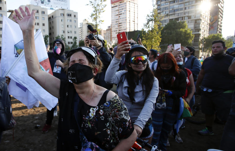 People gather at Plaza Italia on the day Chileans voted in a referendum to decide whether the country should replace its 40-year-old constitution, written during the dictatorship of Gen. Augusto Pinochet, in Santiago, Sunday, Oct. 25, 2020. (AP Photo/Luis Hidalgo)