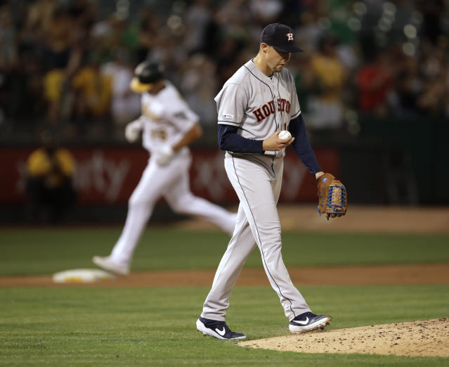 Houston Astros' Aaron Sanchez, right, walks back to the mound after giving up a three-run home run to Oakland Athletics' Matt Olson, rear, in the fourth inning of a baseball game Thursday, Aug. 15, 2019, in Oakland, Calif. (AP Photo/Ben Margot)