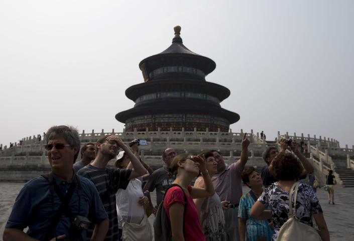 "In this Wednesday, July 31, 2013 photo, a group of foreign tourists visit the Temple of Heaven in Beijing. China's tourism industry has grown at a fast pace since the country began free market-style economic reforms three decades ago. However, it's latest tourism slogan ""Beautiful China"" has been derided as particularly inept at a time when record-busting smog has drawn attention to the environmental and health costs of China's unfettered industrialization. Some point to unsophisticated marketing as an explanation. (AP Photo/Andy Wong)"
