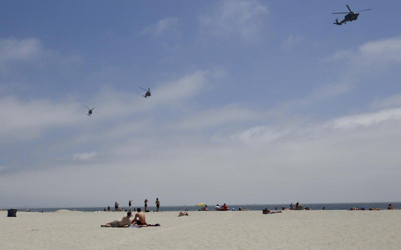 """In this May 22, 2012 photo, part of a Navy helicopter squadron flies over beach goers on the Coronado Beach in Coronado, Calif. The Coronado Beach has been named America's best beach. Coronado Beach tops the 2012 list of Top 10 Beaches produced annually by coastal expert Stephen P. Leatherman, also known as """"Dr. Beach,"""" director of Florida International University's Laboratory for Coastal Research. (AP Photo/Lenny Ignelzi)"""