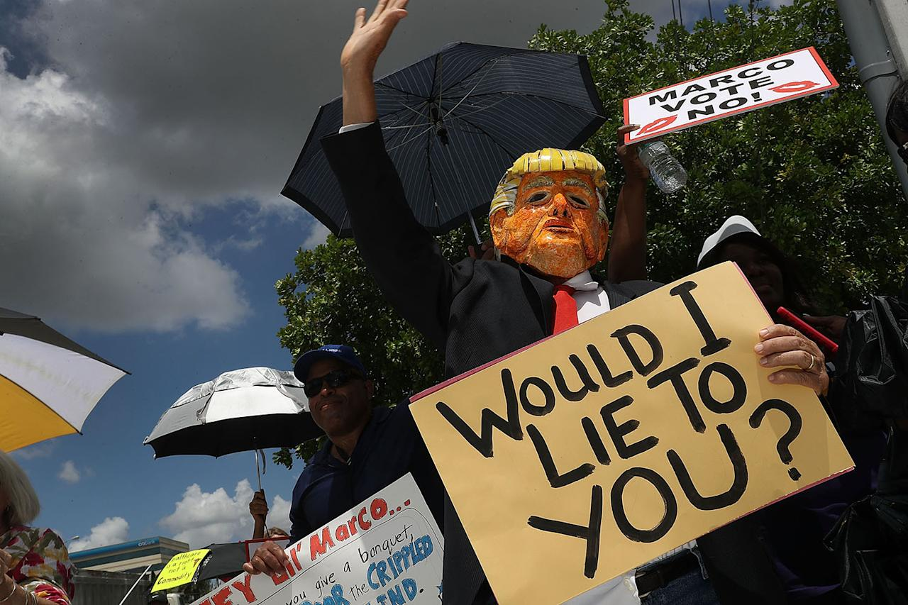 <p>Glenn Terry dressed as President Trump joins with other protesters at Sen. Marco Rubio's office on June 28 in Doral, Fla. (Photo: Joe Raedle/Getty Images) </p>