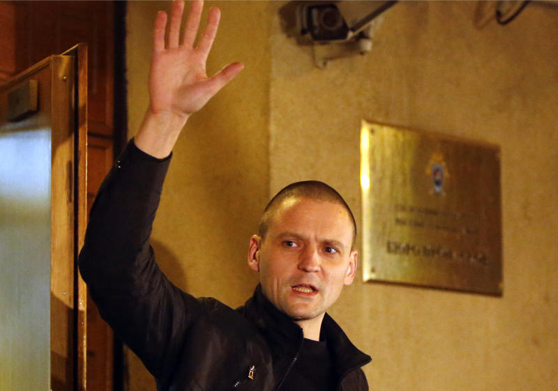 Russian opposition leader Sergei Udaltsov gestures as he leaves the headquarters of the Russian Investigation committee after he was questioned, in Moscow, Wednesday, Oct. 17, 2012. Russia's top investigative agency says it will investigate claims made in a recent documentary aired by a Kremlin-friendly TV channel that opposition leaders worked with Georgian officials to prepare terrorist attacks across Russia. Udaltsov, 35, a leather-clad, shaven-headed leader of the Left Front opposition movement, has denied the charges stemming from the documentary, which he said was a sham. (AP Photo/Misha Japaridze)