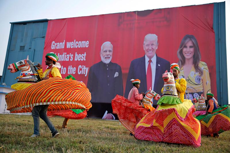 Indian folk dancers rehearse their performance next to a billboard featuring Indian Prime Minister Narendra Modi, U.S. President Donald Trump and first lady Melania Trump at the airport in Agra, India, Sunday, Feb. 23, 2020.