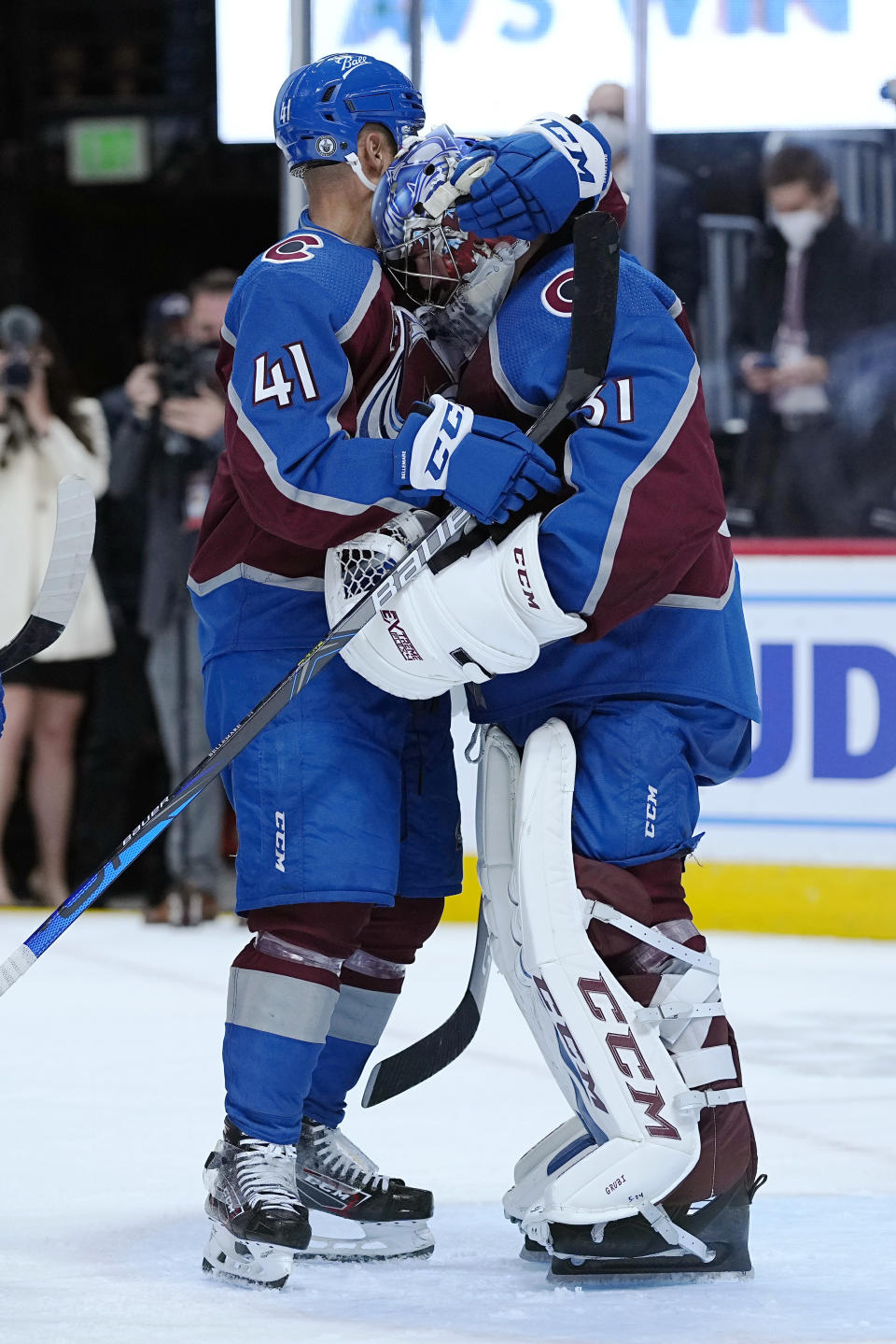 Colorado Avalanche center Pierre-Edouard Bellemare (41) and goaltender Philipp Grubauer (31) celebrate a win against the Vegas Golden Knights after Game 1 of an NHL hockey Stanley Cup second-round playoff series Sunday, May 30, 2021, in Denver. (AP Photo/Jack Dempsey)