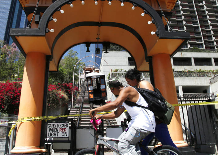 Passersby make their way by Angels Flight in downtown Los Angeles Thursday, Sept 5, 2013. An accident has stopped Angels Flight, the tiny funicular railway that goes up and down a hill in downtown Los Angeles. Fire Department spokeswoman Katherine Main says one of the two rail cars came off its tracks late Thursday morning. (AP Photo/Nick Ut)