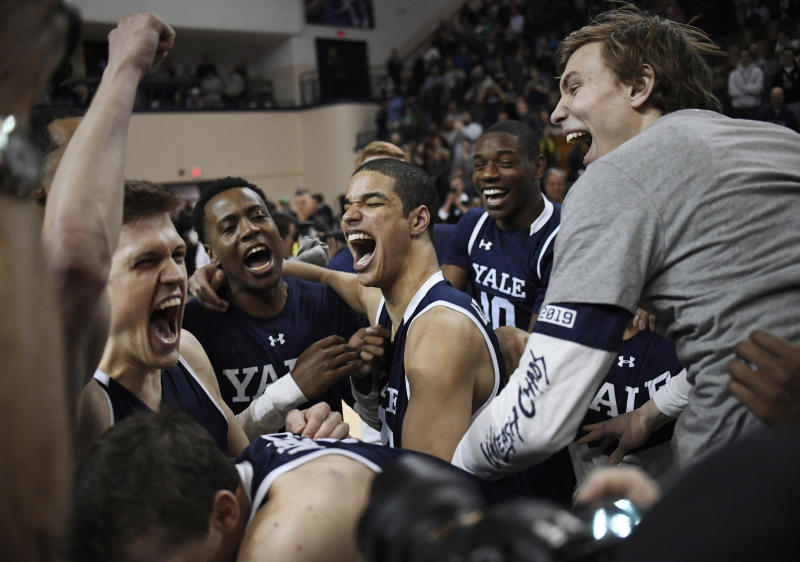 Yale basketball players celebrate their Ivy League championship win over Harvard after an NCAA college basketball game at Yale University in New Haven, Conn., Sunday, March 17, 2019, in New Haven, Conn. (AP Photo/Jessica Hill)