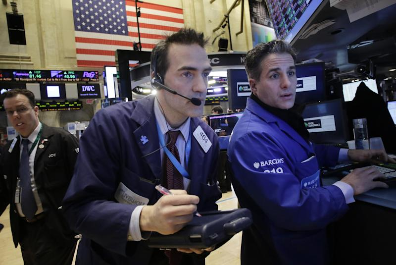 Gregory Rowe, center, places orders for stock with Anthony Rinaldi, right, at the New York Stock Exchange, Wednesday, Feb. 12, 2014. U.S. stocks are edging higher in early trading as the market extends its longest winning streak of the year. (AP Photo/Mark Lennihan)